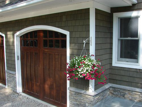 green stained cedar shingles. wood garage door. stone