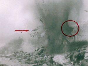 Un obus de mortier explose au milieu des GI's déchiquetant l'un d'eux. On aperçoit le haut d'un corps dans le cercle rouge. La flèche montre un bras ,Les hommes courent pour se mettre à l'abri des tirs et des obus. L'homme au premier plan est bizarrement équipé d'une Mae-West (Life preserver type B.4) et a perdu son arme tandis que le second n'a pas encore enlevé la housse de la sienne. Le sol est déjà jonché de corps. (Col.privée)