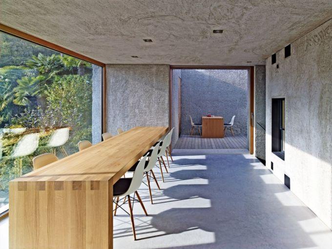 Vzhled nahrubo opracovaného jídelního stolu z dubového masivu ještě umocňují drobné Eamesovy židle na tenkých elegantních nohách. Prosklenou stěnou je vidět do zahrady