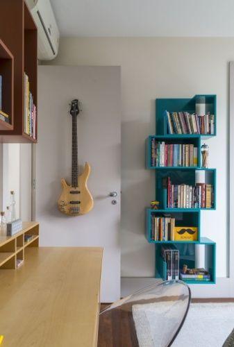 Para completar o quarto idealizado por Eliane Mesquita, uma das paredes foi preenchida com marcenaria executada sob medida em madeira aparente. A estante azul petróleo foi comprada na Marché Art de Vie
