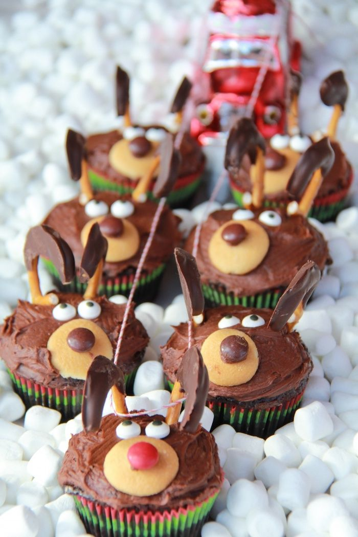 chocolate cupcakes images, seven cupcakes with chocolate frosting, made to look like santa's deer, with biscuits and candies, tied with red and white string to red toy car