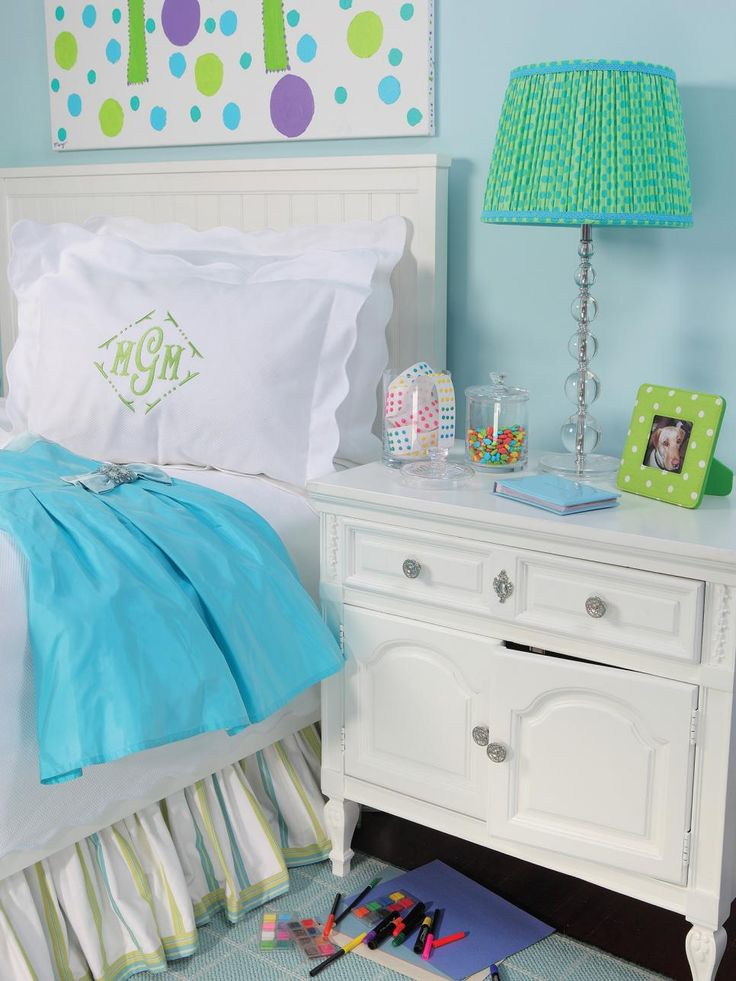 This teen bedroom features light blue walls against a white bed and nightstand. The letters of the monogramed pillow, painted spots on a large hanging canvas and polka dot lamp shade placed on a funky crystal stand coordinate with the green and blue color scheme.