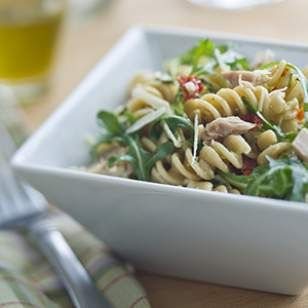To prepare dressing: Combine oil, broth, vinegar, basil, shallots, salt and pepper in a jar with a tight-fitting lid. Shake until well combined. (Or whisk in a bowl.)     To prepare pasta salad: Cook pasta in a large pot of boiling water according to package directions. Drain, transfer to a large bowl and let cool. Add arugula, zucchini, tuna, cheese, tomatoes, pepper and the dressing; toss to coat.