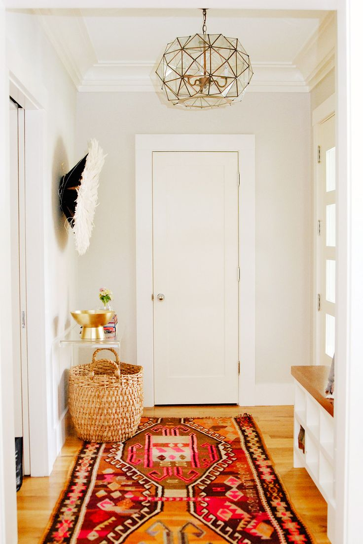 Neutral entryway with glass chandelier and juju hat on wall