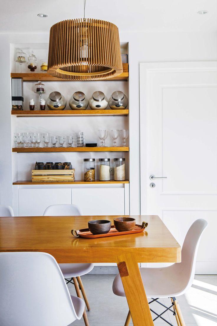 En la cocina de este departamento de Palermo, mesa de madera con sillas blancas y lámpara hecha con varillas, también de madera.