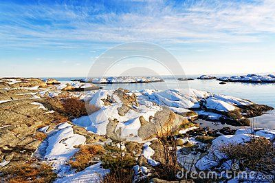 Winter View of the rocky coast of the Norwegian Sea. Snow covered rocks by the water. Visible signs of outflow of the sea. Blue sky. Winter in Aust-Agder municipality. Region of southeastern Norway. North Sea Coast. Skagerrak coastline. Norwegian landscape.