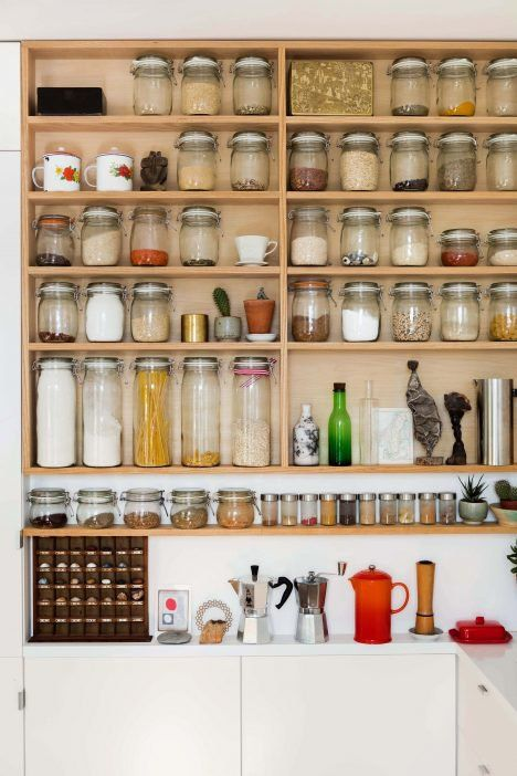 This London flat's shelving system functions as a larder in the kitchen where items are stored in simple glass jars so that their contents are clearly visible.