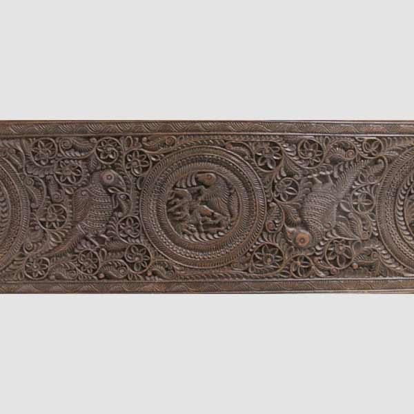 AN ARCHITECTURAL PANEL (detail). Andhra Pradesh, Deccan, Southern India, late 19th century, Carved wood, of rectangular form, the central roundel depicting a boar with her two piglets, two half roundels at either end containing a similar animal, surrounded by profusely scrolling foliage, a parakeet between each roundel