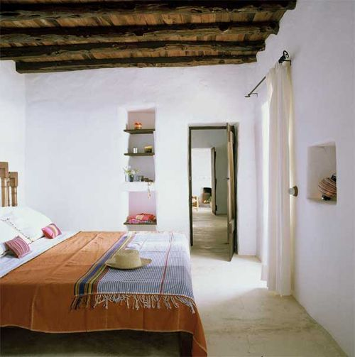 Whitewashed walls, integrated shelving units and unpainted wooden ceiling in Ibiza
