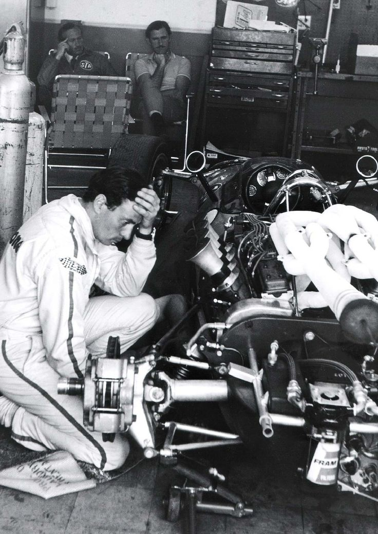 "Jim Clark, Graham Hill & Colin Chapman. It looks like Jim is thinking ""Jeez Colin, I don't know how to put this thing back together""."