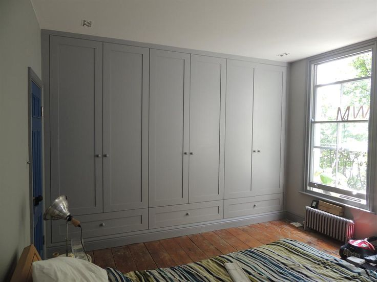 This floor to ceiling fitted wardrobe is made up of three units. It has shaker style doors with a large drawer underneath. The internal unit is made from a coloured MFC. Features soft close hinges and drawer runners.