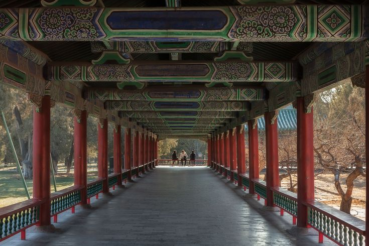 A peaceful view of three men relaxing in the sunshine at the end of a long verandah at the Temple of Heaven in Beijing, China.