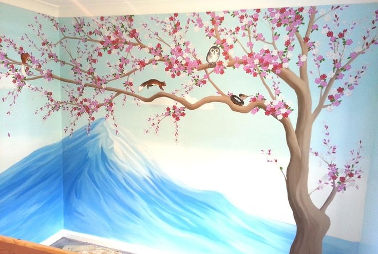This pretty blossom tree mural was hand painted in a little girls bedroom. In the background we painted a snowy mountain with a cool blue sky, then the bloosom tree was painted in the foregroumnd influenced by Japanese illustrations. The cool blue and bright pink really complemented each other and made the colours pop. In the tree we also painted a few little animals such as a squirrel and owl.