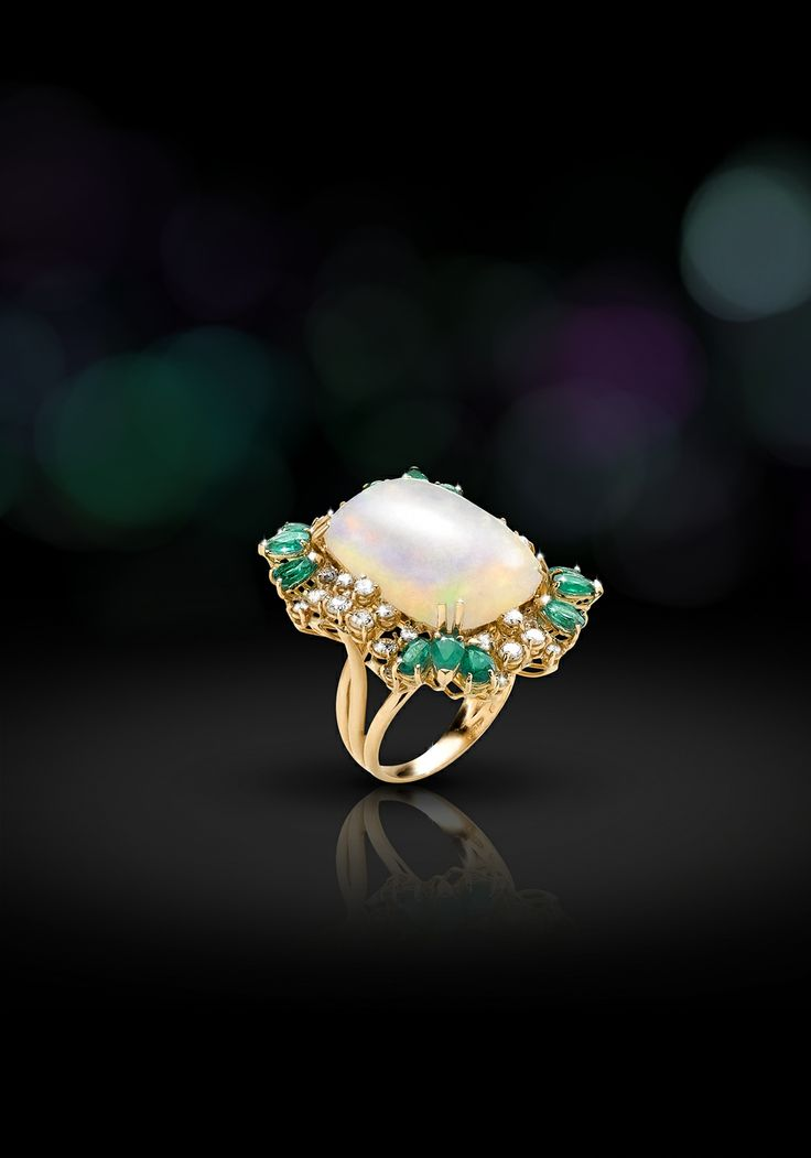 Anello in oro giallo 18 kt contornato con brillanti e smeraldi taglio goccia. Al centro un grande opale australiano. (Ring in 18kts white gold with diamonds and drop emeralds. In the middle australian opal.9  Sortija en oro blanco de 18 kt rodeada de diamantes y gotas de esmeraldas. En el medio un opalo australiano.