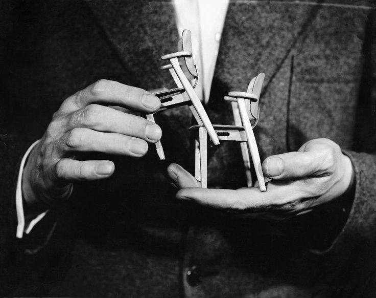 Finnish designer Ilmari Tapiovaara holding two miniature models of his Domus chair, produced originally by Laukaan Puu Oy.
