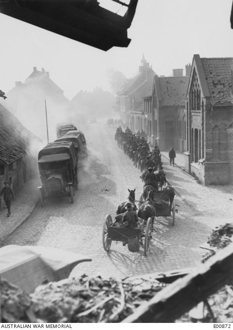 Motor and horse transport passing through Vlamertinghe, near Ypres. Motor transport, including six Australian companies, continuously used the cobbled road from Poperinghe to Ypres. The photograph illustrates the observance of the rule laid down for all roads, the slower vehicles moving in a single column close to the kerb and leaving the centre of the road free for fast traffic.