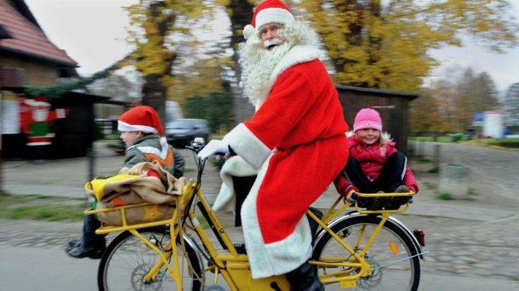 Ein Mann in Weihnachtsmann-Kostüm auf einem gelben Post-Fahrrad. Im Packet-Fach vorne ein kleiner Junger, hinten ein kleines Mädchen.