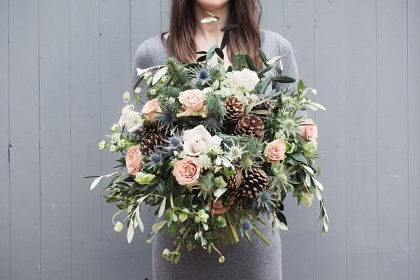 A pale winter bunch, featuring winter cones and pine, with delicate frosty roses and seasonal flowers. This works well!