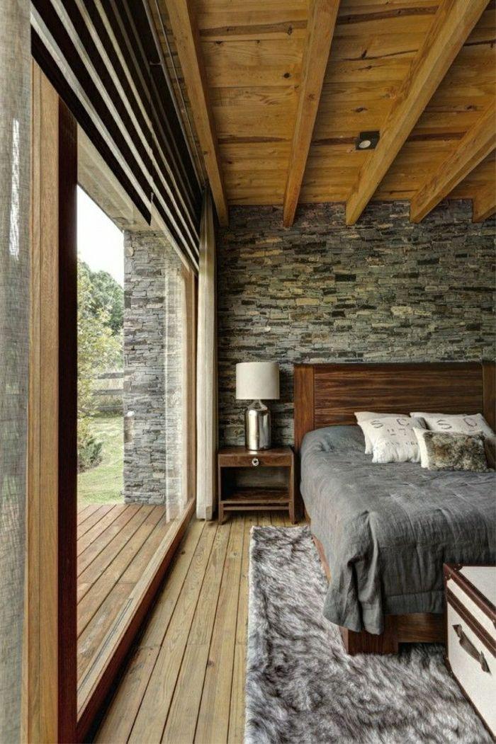 tapis fausse fourrure grsi, plafond en bois, fenetre, chambre lumineuse, mur de pierre gris