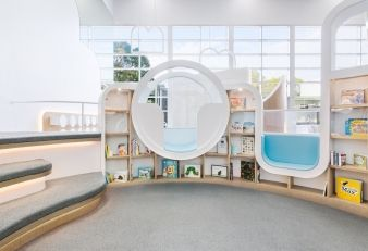 Seating areas blend into the walls and bookshelves of the play centre