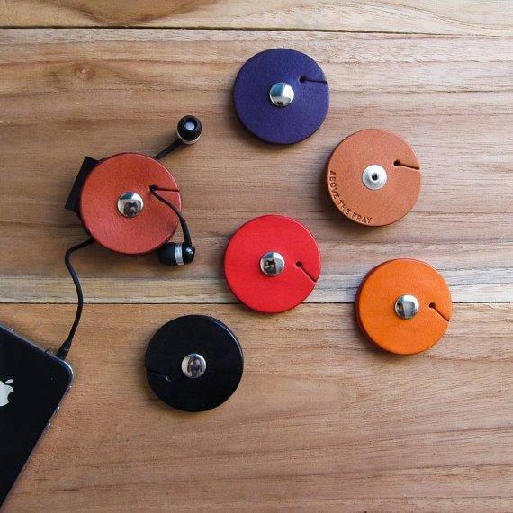 TunePoint, an earbud organizer / holder: vegetable-tanned leather, tan / orange / purple / black / maroon, minimalist, unique