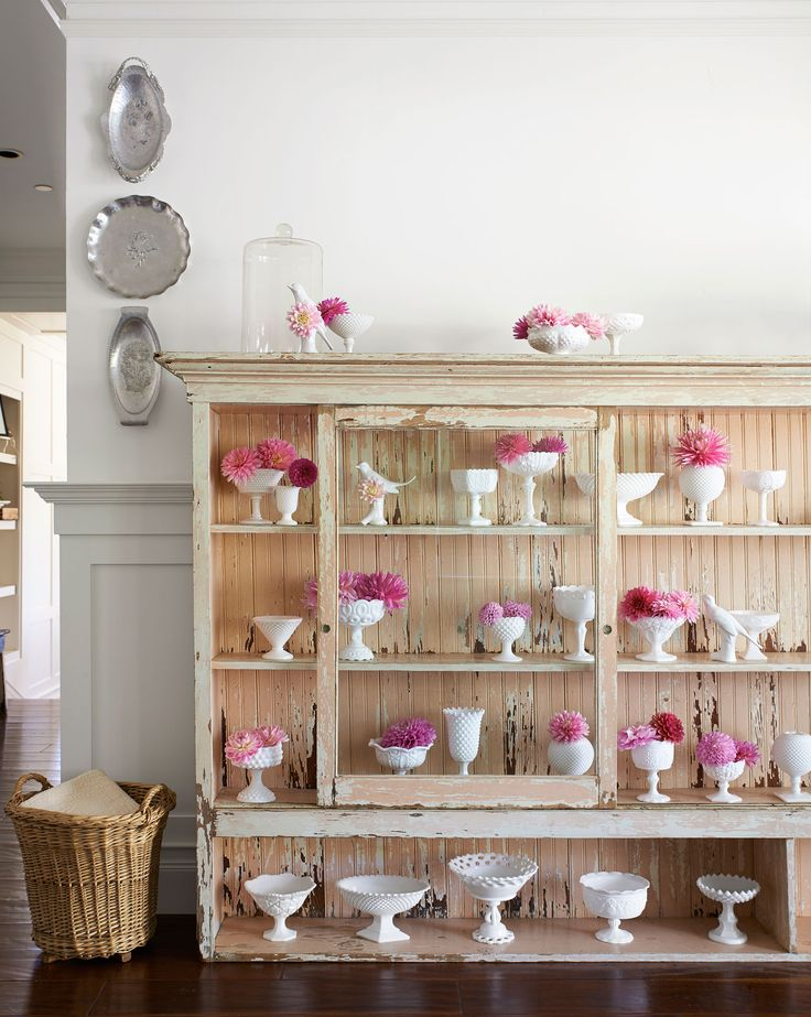 The owner of this elegant farmhouse shows off her milk glass in a general-store display case.   - CountryLiving.com