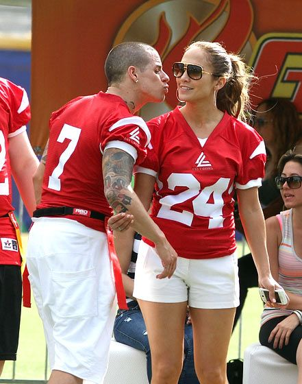 Casper Smart and Jennifer Lopez, in matching red jerseys, puckered up at a Dec. 22 charity football event in Puerto Rico.