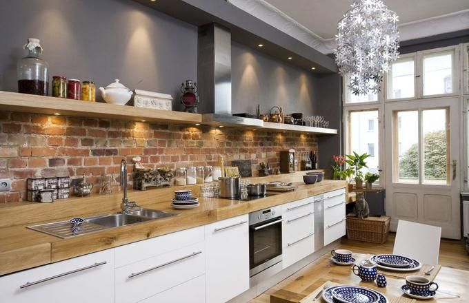 Czerwona cegła nad blatem kuchennych szafek w stylu skandynawskim