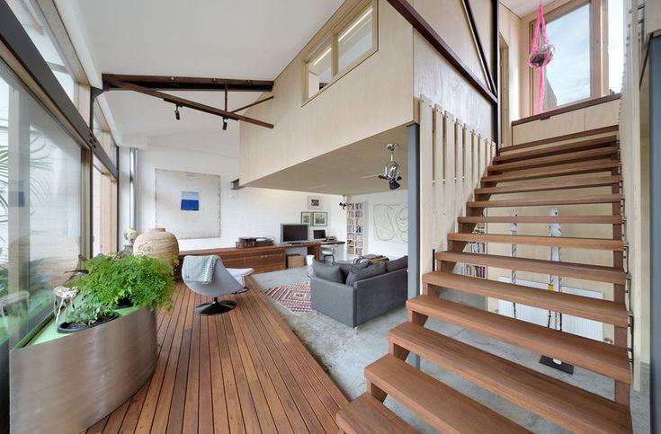 Depuis le séjour de ce loft industriel on accède via l'escalier à la chambre à coucher