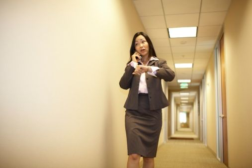 Asian businesswoman talking on cell phone and checking time