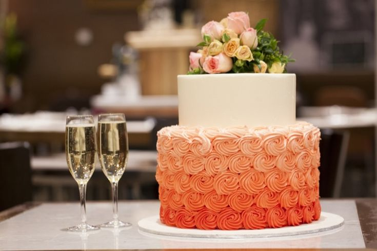 Emozione - Two-tiered cake covered in buttercream and finished off with fresh roses