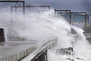 A Scotrail train passes as waves crash against the new weather defences in North Ayrshire, Scotland