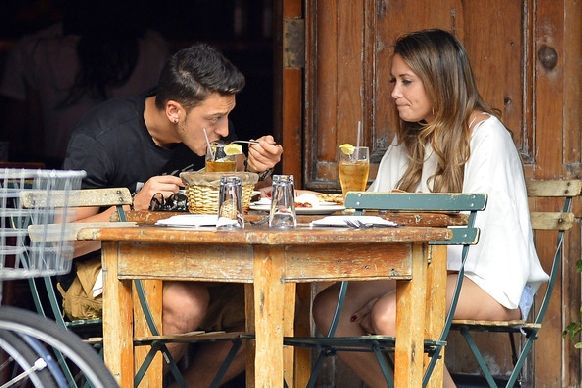 German soccer player Mesut Ozil out in rain with his girlfriend Mandy Capristo in New York City. Mesut and Mandy were seen eating at Morandi restaurant and shopping in the West Village