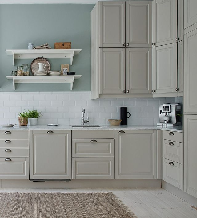 A beautiful peaceful looking Scandinavian kitchen … with pale green walls, stone cabinets and white subway tiles, and a sweet black/brass pendant light. A soft white pigmented wood floor, white wood t