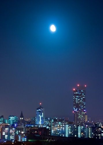 Manchester and the Beetham Tower at night.. Manchester skyline in the night with bright moon.