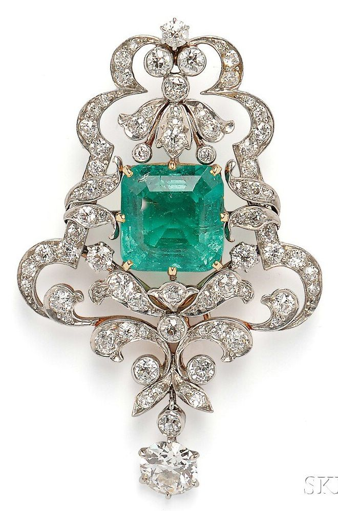 Edwardian Emerald and Diamond Pendant/Brooch, set with a square emerald-cut emerald measuring approx. 12.10 x 11.70 x 8.60 mm, and weighing approx. 8.00 cts., in a scrolling mount set with old European- and old mine-cut diamonds, and suspending an old European-cut diamond weighing approx. 1.00 cts., platinum-topped gold mount. #Edwardian #pendant #brooch