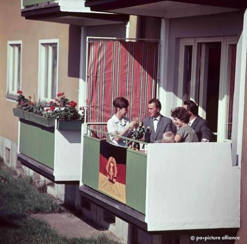 """""""Dream apartment block"""". A family celebrates with the east german flag on the balcony of her new apartment, 1963. In 1964, 90 percent of all homes in eastern Germany were produced industrially. Source: tagesspiegel.de"""