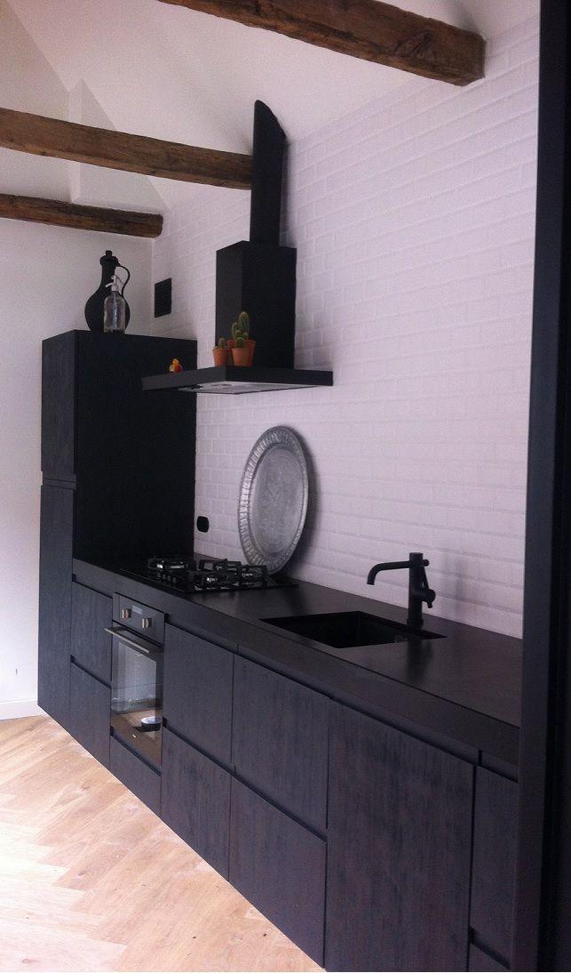 Een stoere industriële keuken op IKEA basis met zwart gelakte en ruw geborstelde fronten. De greeploos bewerking geeft het geheel een moderne uitstraling.