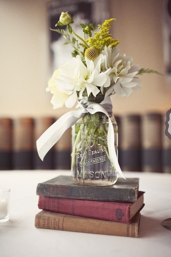Stack a jar or vase on vintage books! Great idea for a future wedding (plus other centerpiece ideas!)