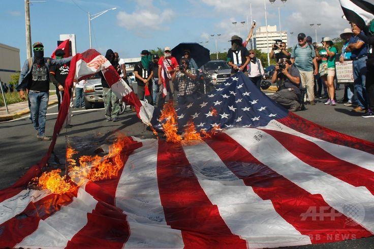 米自治領プエルトリコの首都サンフアン San Juan で、米国の51番目の州への昇格案の是非を問う住民投票に抗議して米国旗を燃やすデモ隊(2017年6月11日撮影)。(c)AFP/Ricardo ARDUENGO ▼12Jun2017AFP|米領プエルトリコ住民投票、「51番目の州」昇格を97%が支持 http://www.afpbb.com/articles/-/3131665