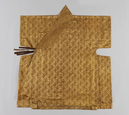"""Dappo is a wide coat with short straight sleeves. This single layered coat is made of satin damask with a cloud and treasure pattern. The length is short in the front and long in the back. The maroon color breast ties are detachable, and not sewn to the coat. It represents an distinctive form of Dappo of early Joseon Dynasty."" Dated 1508-1572. At the  Seok Juseon Memorial Museum, Dankook University, via the Google Cultural Institute."