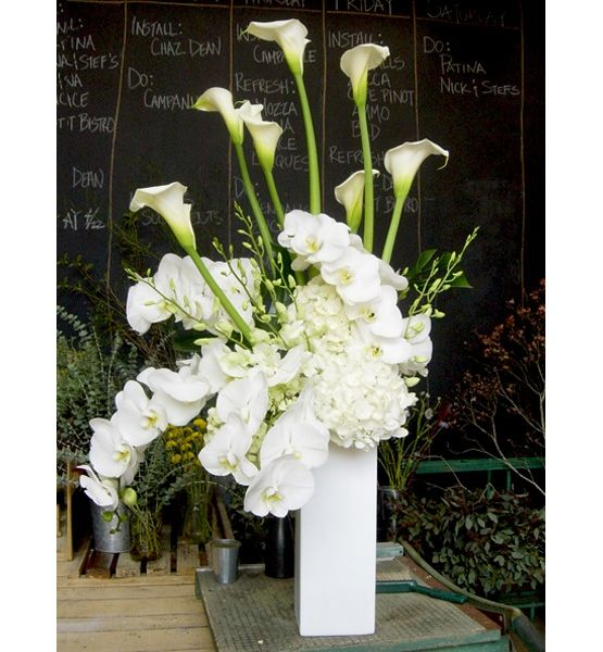 """White Out  Once only for weddings and parties, the monochromatic look now comes home in simple, clean-lined containers, whether square, rectangular or cylindrical. """"Choose three to five florals in one color: one with clean lines like calla lily, one that has curve like orchids, and one that is bulky like hydrangeas,"""" says Clover."""