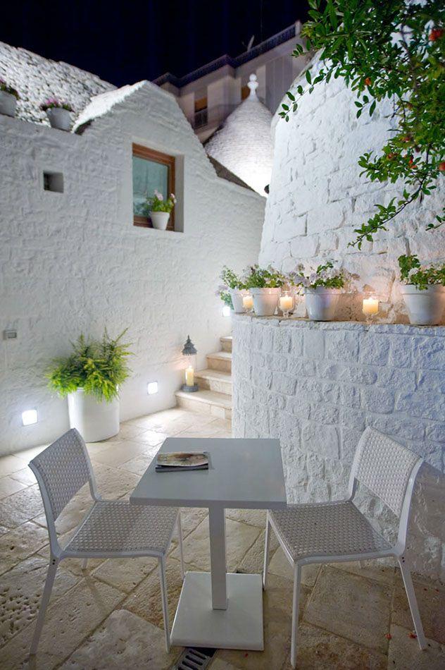trulli esterno luci incasso muro vasi bianco tavolino sedie bianco