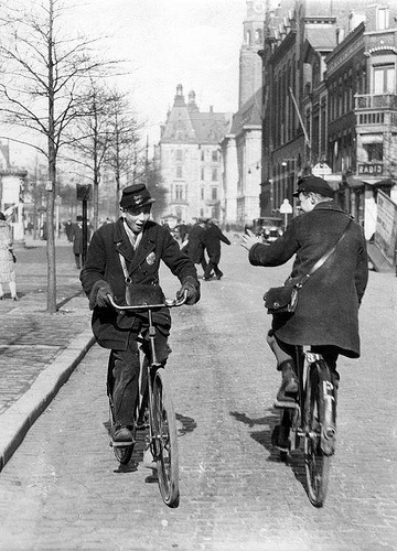 Telegram deliverers on bicycle greeting each other in the street. [Coolsingel, Rotterdam], The Netherlands, early 1930s.