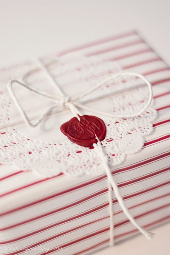 red striped paper, white doily and a wax seal with kitchen twine....perfect! Thanks for giving me wrapping idea for next Christmas! LOL