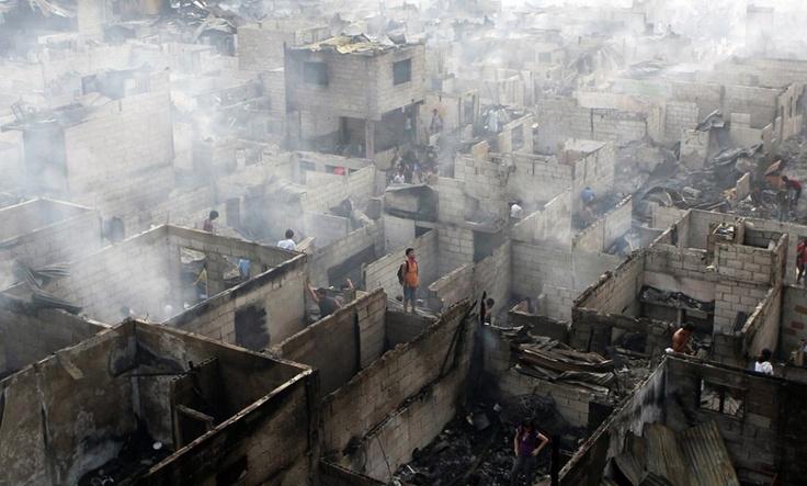 Bewoners lopen door de restanten van hun huizen. Die zijn is as gelegd door een enorme stadsbrand in Makati City op de Filipijnen. Ruim tweeduizend families bleven dakloos achter. (april)