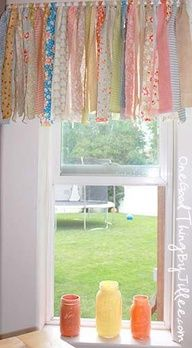 "These are just coordinated fabric ""fat quarters"" from JoAnn tied to a white curtain rod. I love this idea, what a great way to bring both bright and light colors together"