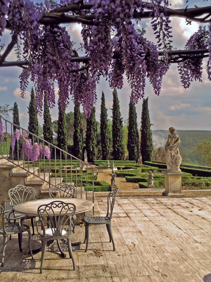 Table under Wisteria overlooking La Selva Vacation Villas, Siena, province of Siena, Tuscany region Italy