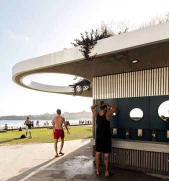 A communal cast concrete wash basin and outdoor showers extend the amenity of the building