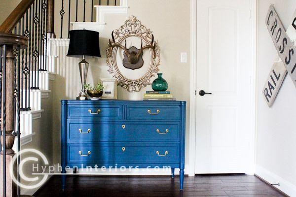 Bright blue painted dresser, light walls, dark floors